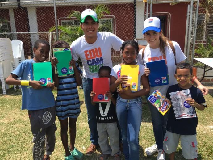 Foto Lucas y Laura junto con los niños que recibieron los cuadernos de cambio